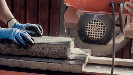 Foto de Workman using an angle grinder to cut a concrete block in a side view of his hands and the power tool, retro effect faded look. - Imagen libre de derechos