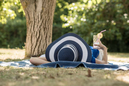 Foto de Woman spending a relaxing day in the garden lying in the shade of a tree in her large brimmed sunhat with a cold cocktail in her hand. - Imagen libre de derechos