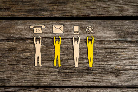 Photo for Teamwork and customer service concept with cut outs of four men supporting a line of phone, web and mail icons from below over a rustic background. - Royalty Free Image
