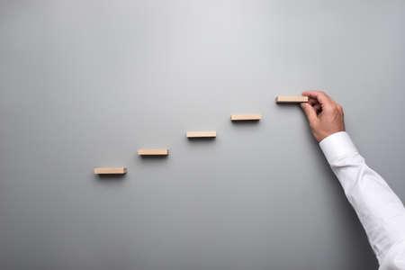 Photo pour Businessman in white shirt building a graph or ladder of success on grey background. - image libre de droit