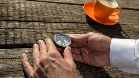 Hands of a man holding compass next to orange coffee cup over old rustic wooden table.