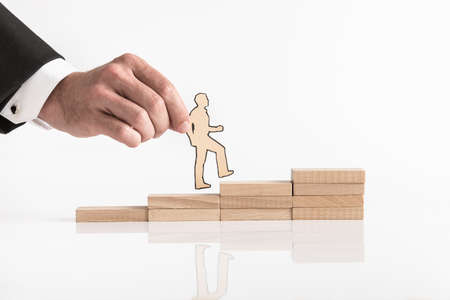 Foto de Businessman holding a cutout of a man walking up steps formed by stacked wooden blocks in a concept of promotion and career success. - Imagen libre de derechos