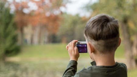Foto de Boy photographing nature with a compact camera outdoors at park. - Imagen libre de derechos