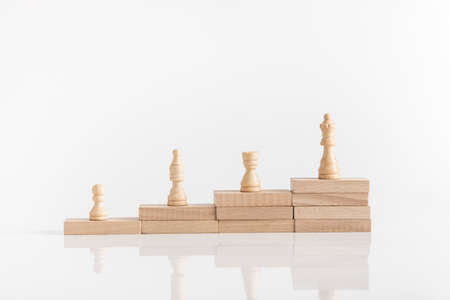 Foto de White chess pieces on a stepped stack of wooden blocks with queen piece on the highest level in conceptual image. - Imagen libre de derechos