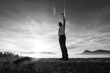 Photo for Businessman holding aloft his fist at sunrise celebrating his success and achievement as he stands on a wall with a misty mountain scene silhouetted against the bright sky, monochrome image. - Royalty Free Image