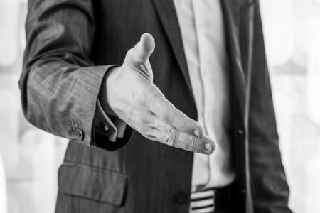 Photo for Black and white image of a businessman in a suit offering his hand in handshake. Closeup view. - Royalty Free Image