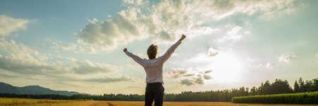 Foto de Panoramic image of successful businessman standing under majestic sky with his arms raised up high in triumph. - Imagen libre de derechos