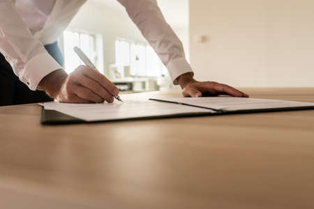 Photo pour Businessman standing at his desk leaning to sign a legal or insurance document in an open folder. - image libre de droit