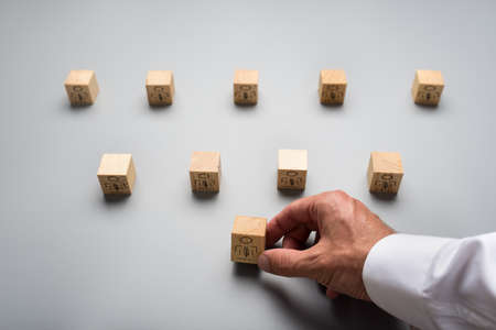 Photo pour View from above of a businessman arranging wooden cubes with people icon on grey background. Conceptual of human resources. - image libre de droit