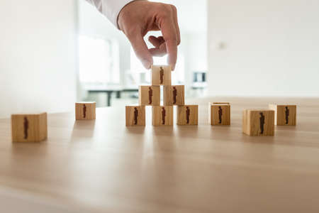 Photo pour Businessman arranging wooden cubes with people silhouette in a pyramid shape with others scattered on office desk. Conceptual of business organization, human resources and teamwork. - image libre de droit