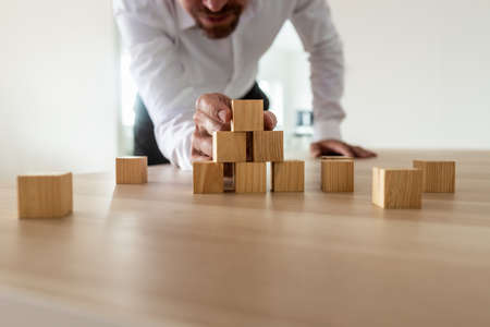 Foto de Businessman leaning in to carefully assemble pyramid shape with blank wooden blocks on office desk. Conceptual of business start up and  vision. - Imagen libre de derechos