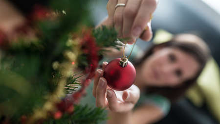Photo for View from above of a woman placing red holiday bauble on Christmas tree with focus to he ball. - Royalty Free Image