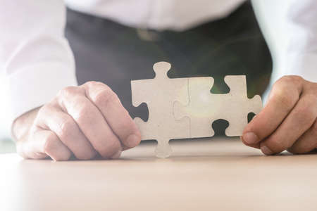 Foto de Closeup view of businessman holding two joined puzzle pieces leaning on his office desk. - Imagen libre de derechos