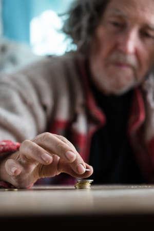Foto de Senior homeless man stacking and counting coins on desk in a conceptual image. - Imagen libre de derechos