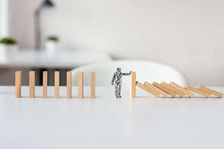 Foto de Hand drawn shape of businessman stopping domino effect in a conceptual image of solving business crisis. - Imagen libre de derechos