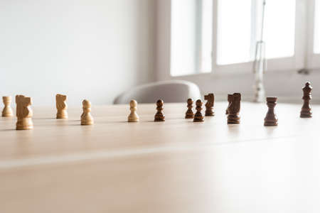 Foto de Black and white chess pieces teamed up and facing each other on a wooden office desk in a conceptual image of business competition. - Imagen libre de derechos