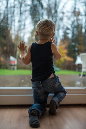 Photo pour Toddler boy standing next to a window looking out to observe nature. - image libre de droit