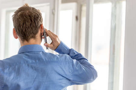 Photo for View from behind of a businessman talking on a mobile phone facing the windows in a bright office. - Royalty Free Image