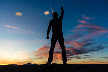 Photo for View from behind of a man standing on top of a wall with his arm raised high in triumph under a beautiful glowing evening sky. - Royalty Free Image