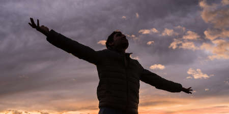 Foto de Low angle view of young man standing under glowing evening sky with his arms outstretched celebrating life and freedom. - Imagen libre de derechos
