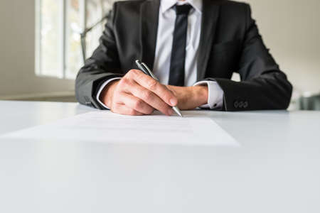 Photo pour Front view of businessman or employer sitting at his office desk signing a contract or employment paper with a pen. - image libre de droit