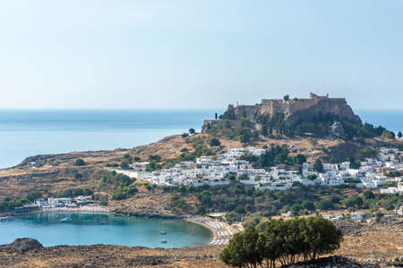 Photo for View of an ancient Greek acropolis of Lindos above the bay of a beautiful blue ocean. - Royalty Free Image