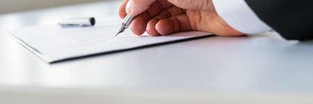 Photo pour Closeup of businessman signing contract with ink pen. - image libre de droit
