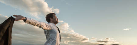 Foto de Wide view image of businessman holding his suit jacket standing under cloudy sky with his arms spread widely celebrating his success. - Imagen libre de derechos