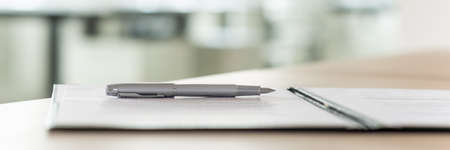 Photo pour Wide view image of an ink pen lying on a contract in an open folder. - image libre de droit