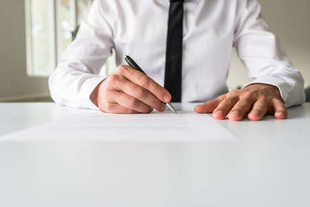 Photo pour Front view of businessman at his office desk signing a document, contract or application form. - image libre de droit