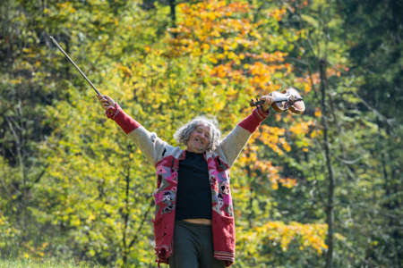 Foto de Happy homeless senior man in torn sweater enjoying life holding his violin with trees in background. - Imagen libre de derechos