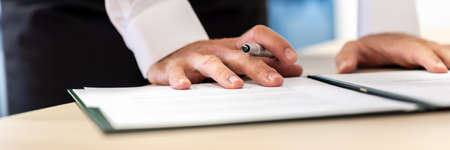Photo pour Wide view image of businessman holding ink pen leaning on a document in a folder proofreading before signing it. - image libre de droit