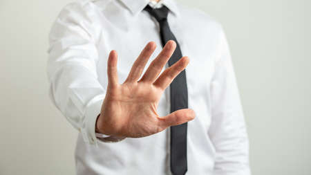 Foto de Front view of a businessman making a stop gesture with his hand towards the camera. - Imagen libre de derechos