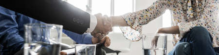 Photo for Wide view image of businessman and businesswoman shaking hands in agreement as the sit in a meeting at an office coffee desk. - Royalty Free Image