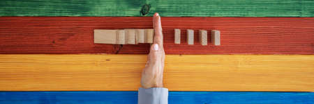 Foto de Top view of male hand intervening to stop dominos from falling in a conceptual image. Over colorful background of wooden planks - Imagen libre de derechos