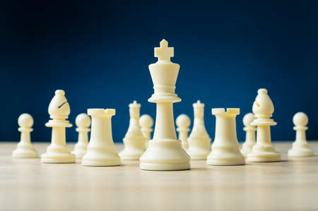 Foto de White chess pieces with the king as the leader placed on wooden desk in a conceptual image. Over blue background. - Imagen libre de derechos