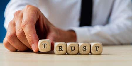 Foto de Hand of a businessman assembling the word Trust spelled on wooden dices. - Imagen libre de derechos