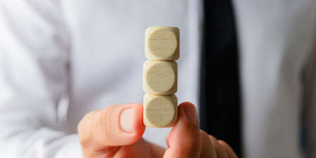Foto de Closeup of businessman holding three stacked blank wooden dices in his hand showing it to the camera. - Imagen libre de derechos