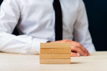 Foto de Businessman sitting at his desk with four stacked wooden pegs on it. - Imagen libre de derechos