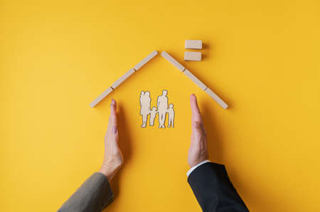 Foto per Male and female hands placed to form a home for paper cut silhouette of a family in a conceptual image. Over yellow background. - Immagine Royalty Free