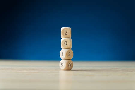 Photo pour Four wooden dices stacked carrying a 2019 sign turning into 2020. Over blue background. - image libre de droit