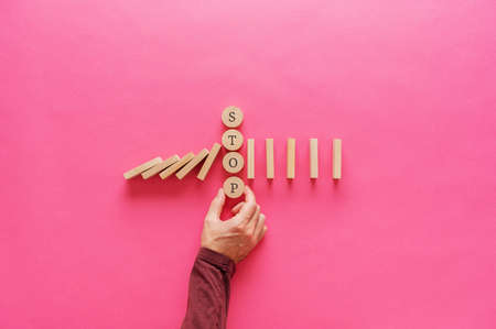 Photo pour Male hand interrupting falling dominos by placing stop word spelled on wooden cut circles in between. Over pink background with copy space. - image libre de droit