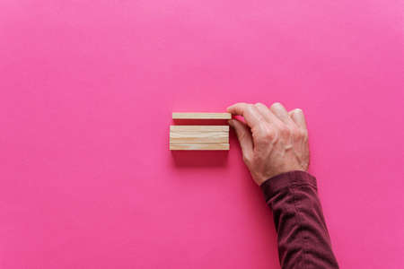 Foto de Male hand stacking blank wooden pegs in a conceptual image. Over pink background with copy space. - Imagen libre de derechos