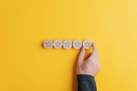 Foto de Male hand placing five wooden cut circles with stars on them in a row over bright yellow background. Conceptual image of quality and service. - Imagen libre de derechos