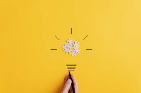 Photo pour Light bulb of blank puzzle pieces as the bulb and hand drawn neck and rays over yellow background in a conceptual image of vision and idea. - image libre de droit