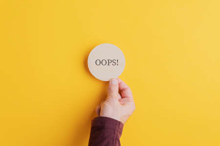 Foto de Male hand placing wooden cut circle with an Oops sign on it on bright yellow background. - Imagen libre de derechos