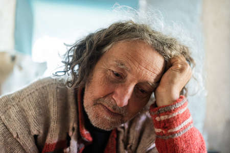 Foto de Portrait of a senior man in torn sweater with worried and tired expression on his face leaning in his arm. - Imagen libre de derechos
