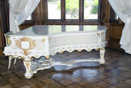 White ancient grand piano trimmed by gold (job of the Italian masters 1700-1800)