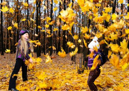 Children in autumn forest. Play fallen down leaf