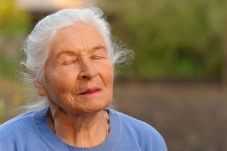 Photo pour The elderly woman with closed eyes. A photo outdoors - image libre de droit